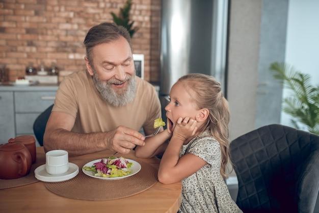 Déjeuner. famille prenant le petit déjeuner ensemble et papa essayant de nourrir son daghter