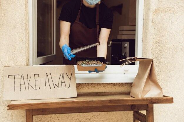 Le déjeuner. femme préparant des boissons et des repas, portant un masque protecteur et des gants. service de livraison sans contact pendant la pandémie de coronavirus de quarantaine. concept à emporter. tasses, emballages recyclables.