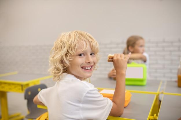 Le déjeuner. un garçon en train de déjeuner dans la classe et l'air satisfait