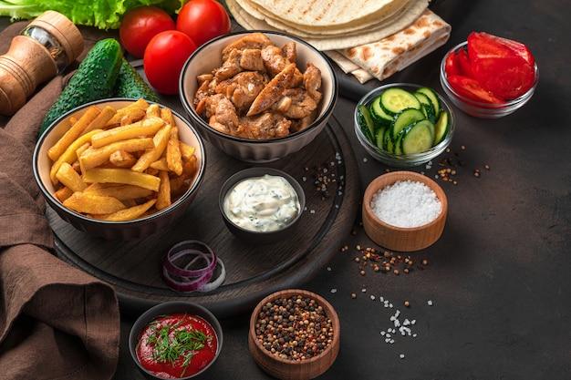 Déjeuner ou ingrédients pour shawarma, burritos, gyroscopes sur un mur marron. vue latérale, copiez l'espace.