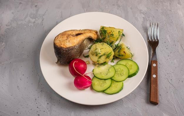 Déjeuner léger avec truite de mer, pommes de terre, concombres, radis et herbes