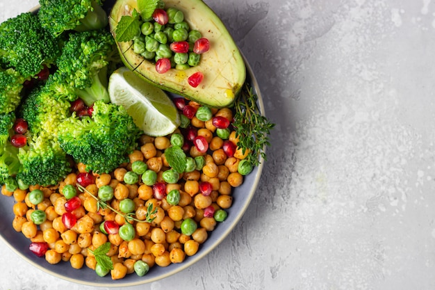Déjeuner de légumes de brocoli, pois chiches, avocat, pois verts, grenade, citron vert et menthe