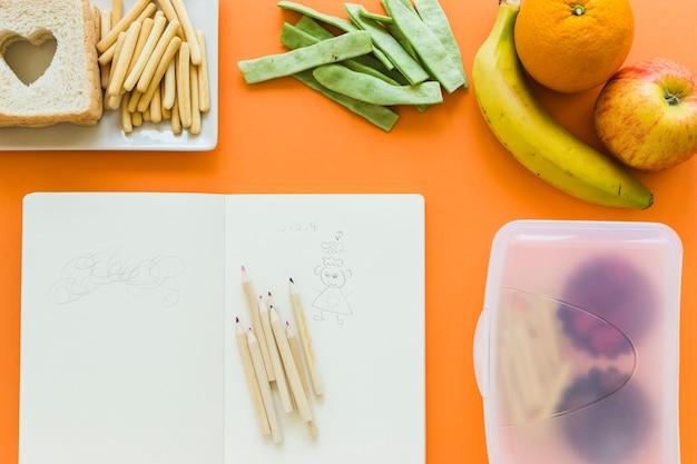 Déjeuner de nourriture près de bloc-notes avec des doodles