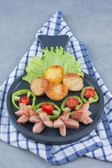 Déjeuner parfait. saucisse frite et pomme de terre sur une poêle.