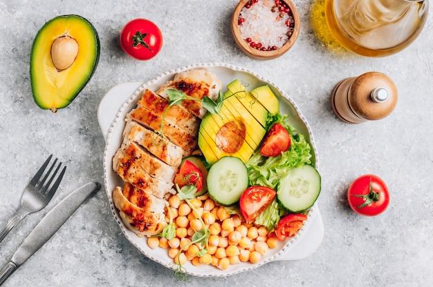 Déjeuner sain de bol de bouddha aux légumes avec poulet grillé et pois chiches.
