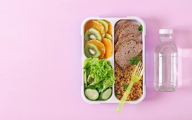 Déjeuner sain avec boulghour, viande et légumes frais et fruits sur fond rose.