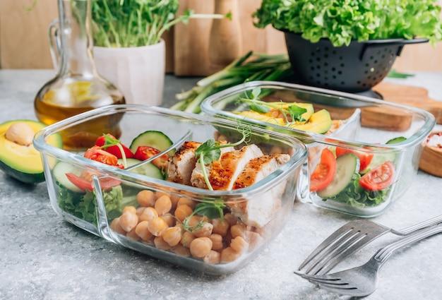 Déjeuner sain dans des récipients en verre sur une table gris clair. .
