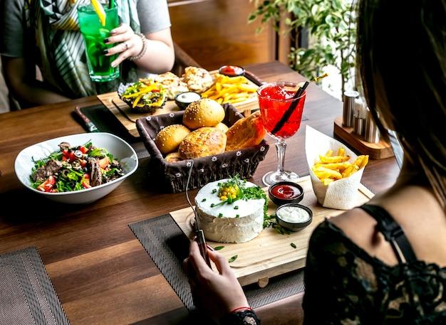 Déjeuner avec salade, plats principaux, pain et boissons vue latérale