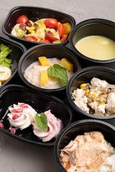 Déjeuner savoureux dans des récipients en plastique sur une table grise
