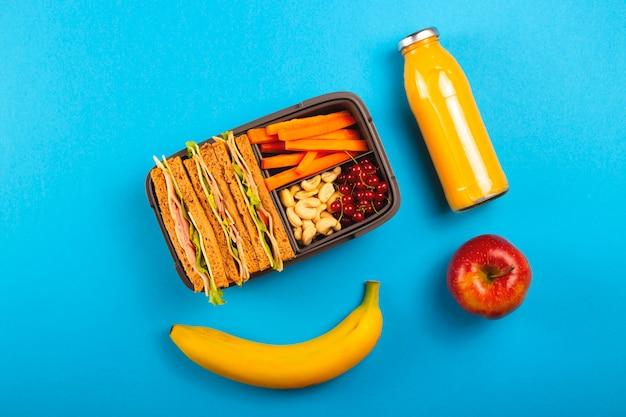 Déjeuner scolaire sain dans un récipient pratique sur un fond bleu vif.
