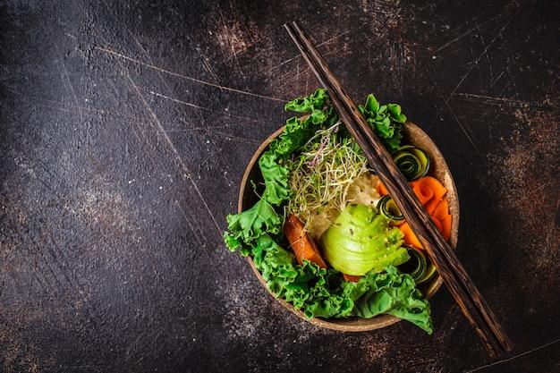 Déjeuner végétalien sain dans un bol de noix de coco. bol de bouddha sur un fond sombre.