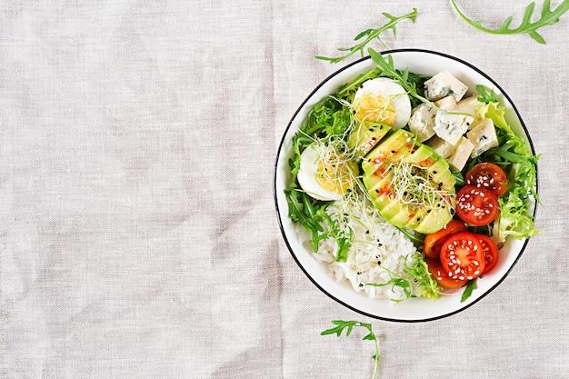 Déjeuner végétarien avec un bol de bouddha avec des œufs, du riz, des tomates, des avocats et du fromage bleu sur la table.
