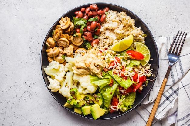 Déjeuner végétarien. riz brun aux champignons, haricots, salade et houmous dans une assiette noire, propre à manger.