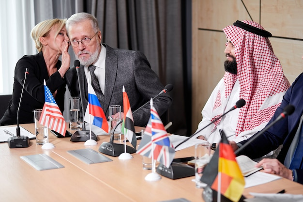 Des délégués caucasiens partageant leurs opinions sur le discours de leurs collègues, des femmes adultes parlent de quelque chose à l'oreille d'un homme barbu gris senior en costume, discutant tandis qu'un groupe multie-thnic de cadres est assis avec eux