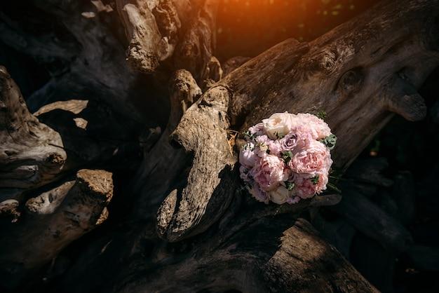 Délicat bouquet de fleurs roses se trouve sur un tronc d'arbre
