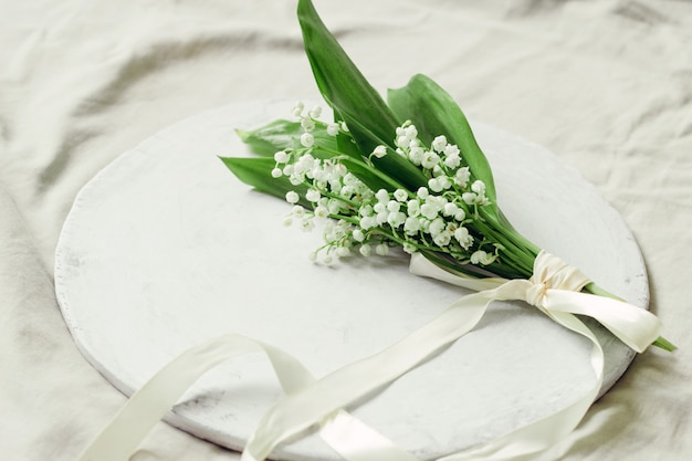 Délicat bouquet de lys frais de la vallée décoré avec un ruban de soie