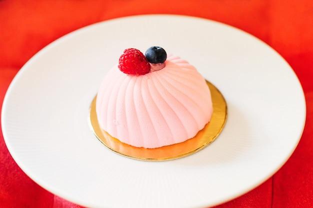 Délicat mini gâteau rose sur une grande assiette blanche une assiette de dessert sur une douce chaise rouge