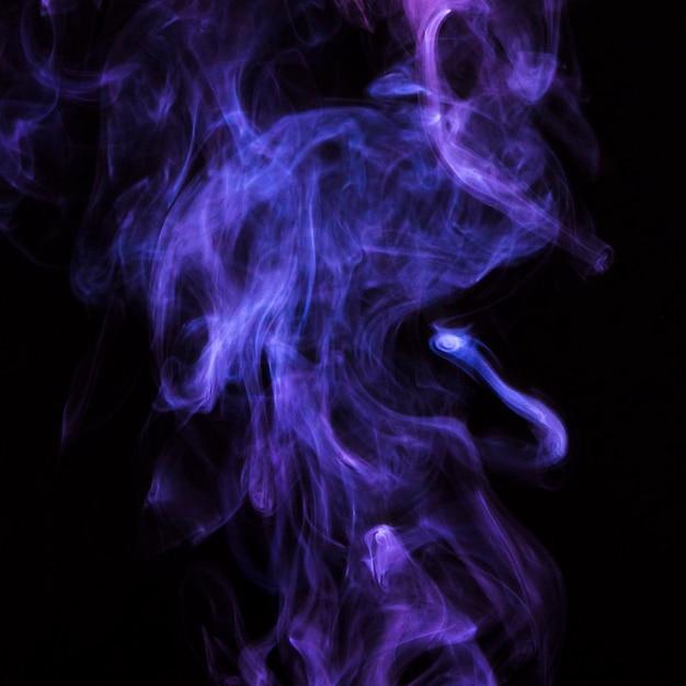 Délicat mouvement de fumée de cigarette mauve sur fond noir