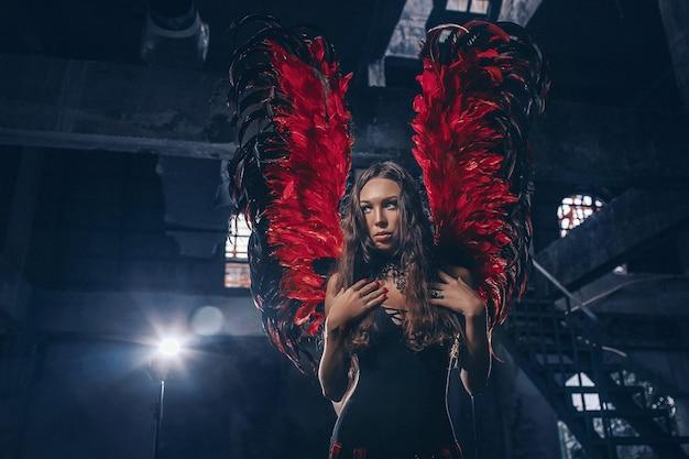 Délicate belle femme brune posant avec des ailes d'ange sombre rouge. tourné en studio.