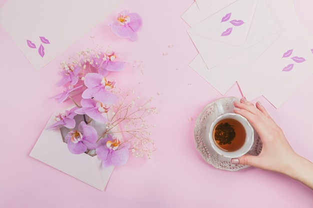 Délicate composition flatlay avec tasse de thé du matin, sac de lettre rose plein de fleurs d'orchidées pourpres et enveloppe vide sur rose clair