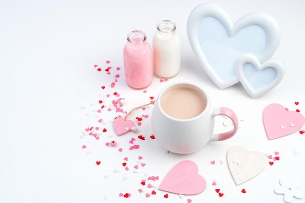 Délicate composition romantique pour le 14 février avec une tasse de café, cadre, coeurs en blanc et rose