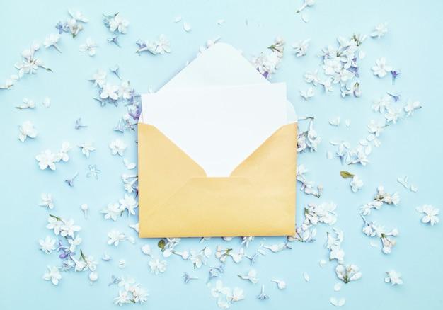Une délicate enveloppe jaune pour les lettres, repose sur un fond clair avec des fleurs lilas.