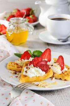 De délicates gaufres belges appétissantes à la crème de fraises aromatisées aux cacahuètes et au miel