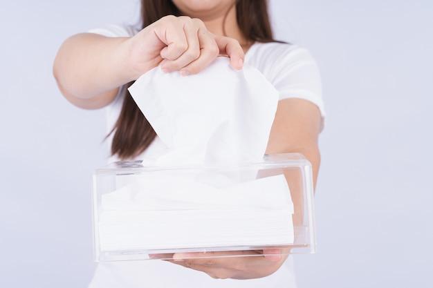 Délicates mains féminines tirant un papier de soie blanc hors d'une boîte de mouchoirs en cristal transparent