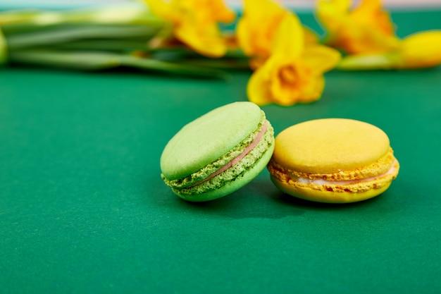 Délicatesse française, macarons colorés avec des fleurs de printemps. bouquet de fleurs de narcisse