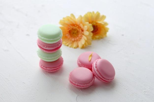 Une délicatesse sucrée française, une variété de macarons colorés en gros plan avec des fleurs sur fond blanc. texture colorée de macaron savoureux.