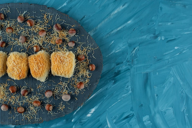 Délices turcs aux noix de macadamia sur une pièce en bois sombre.