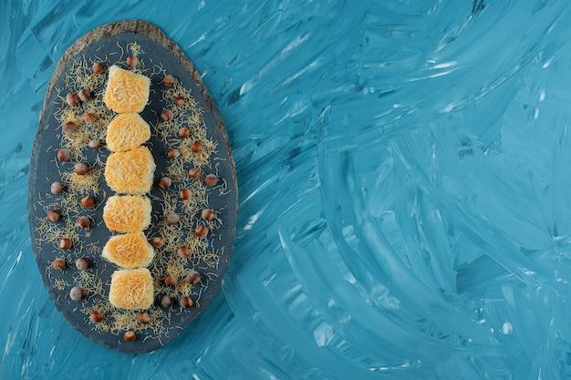 Délices turcs aux noix de macadamia sur une pièce en bois sombre