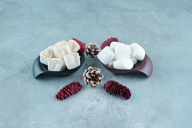 Délices turcs et guimauves dans de petits bols à côté de pommes de pin sur marbre.