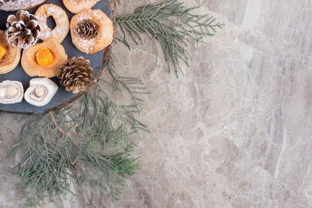 Délices turcs, pommes de pin et biscuits en forme d'anneau sur marbre.