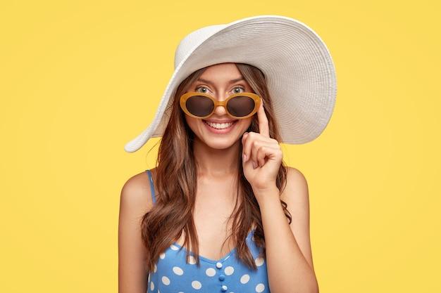Délicié jeune femme portant un chapeau posant contre le mur jaune