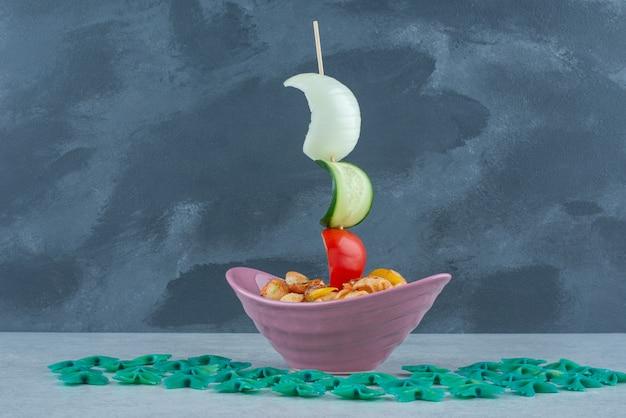 Délicieuse assiette rose avec macaronis sur fond sombre. photo de haute qualité