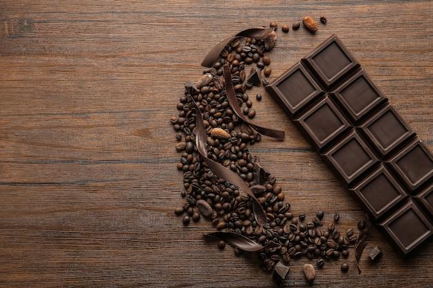 Délicieuse barre de chocolat, copeaux et grains de café sur table en bois