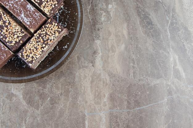Délicieuse barre de chocolat gaufré avec noix sur plaque sur marbre.