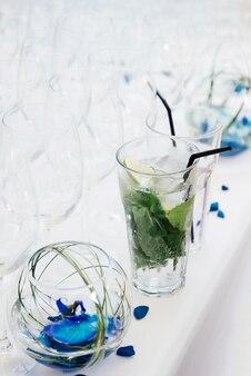 Une délicieuse boisson fraîche d'eau au citron vert et à la menthe se dresse sur une table avec une nappe blanche et des plats vides