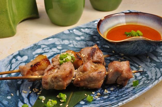 Délicieuse brochette de porc asiatique sur feuille de bananier avec sauce