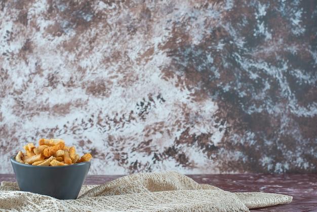 Délicieuse chapelure croustillante dans un bol sur une nappe, sur la table en marbre.