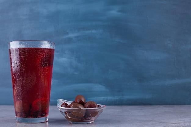 Délicieuse confiture de fruits avec une tasse en verre de thé noir placé sur un fond coloré.