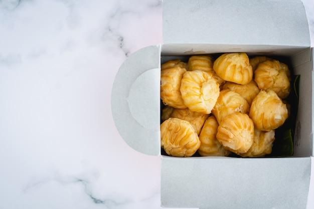 Délicieuse crème à la vanille eclair, pâte à choux remplie d'une crème, boulangerie maison dans un emballage en carton sur fond de marbre blanc pour le concept de collation