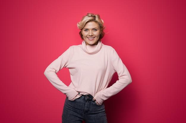Délicieuse femme de race blanche aux cheveux blonds, souriant à la caméra dans un pull rose sur un mur rouge