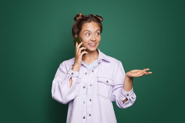 Délicieuse femme de race blanche portant une chemise moderne parlant au téléphone pose sur un mur vert