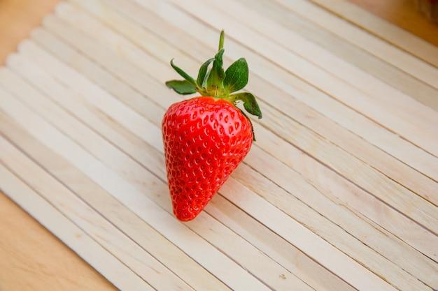 Délicieuse fraise sur napperon en bois et bois clair. vue grand angle.
