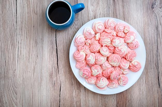 Délicieuse meringue bicolore aérée sur une assiette avec une tasse de café. vue de dessus, mise à plat avec espace de copie.