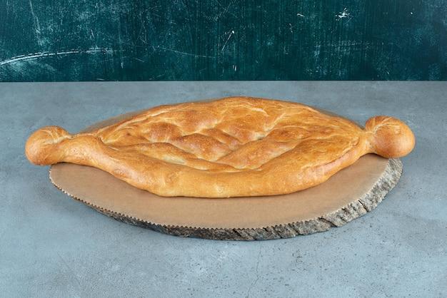 Délicieuse miche de pain sur morceau de bois.