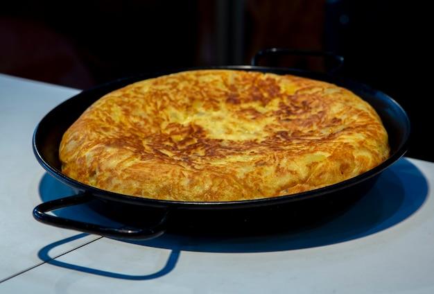 Délicieuse omelette aux pommes de terre typique de la cuisine espagnole préparée dans une poêle à paella avec mise au point sélective