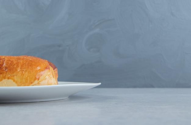 Délicieuse pâtisserie aux saucisses sur plaque blanche.